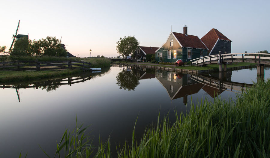 Zaanse schans, Holland - Traditional Dutch village Architecture Beauty In Nature Built Structure Canal Clear Sky Day Grass Green Color Growth Nature No People Outdoors Plant Reflection Sky Standing Water Tranquil Scene Tranquility Water