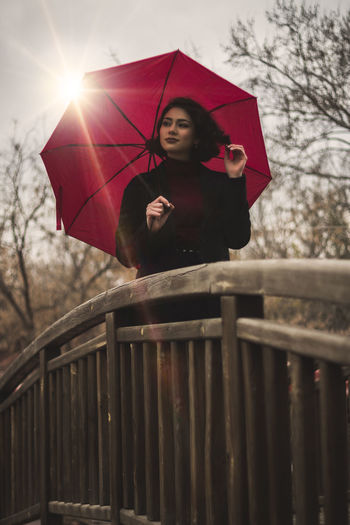 Full length of woman standing on railing during rainy day