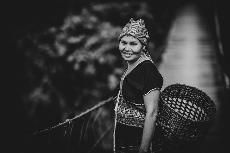 Portrait Of Smiling Woman Carrying Basket While Standing On Footbridge