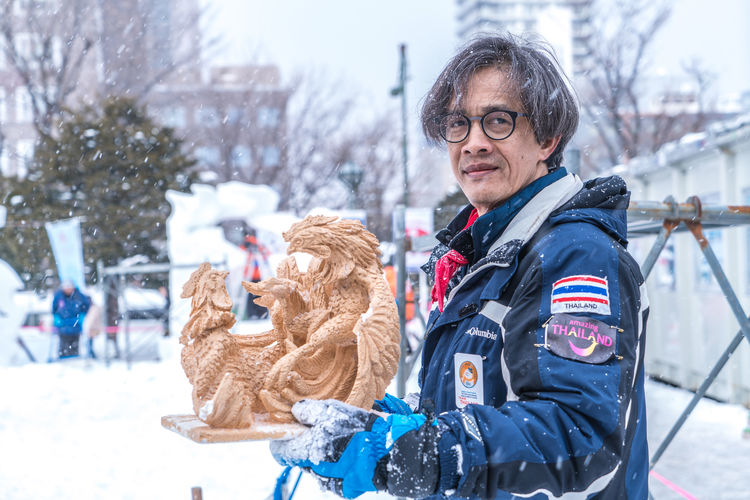 Thailand - Sapporo Snow Festival 2018 Hokkaido Japan Thai Thailand Adult Clothing Cold Temperature Day Domestic Animals Eyeglasses  Focus On Foreground Glasses Looking At Camera Mammal One Person Outdoors Portrait Real People Sapporo Smiling Snow Snowing Waist Up Warm Clothing Winter