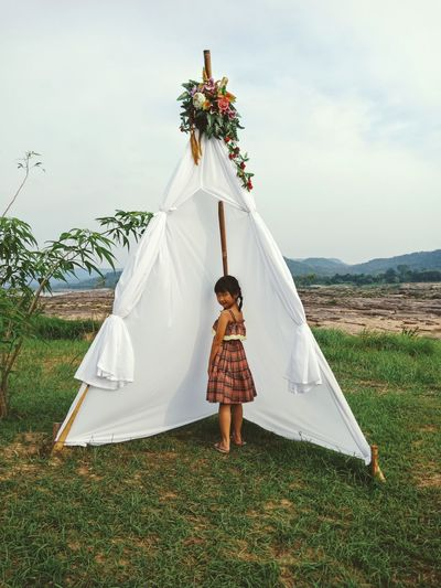 Portrait of girl standing by tent on land