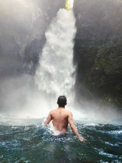 Rear View Of Shirtless Man Looking At Waterfall In River