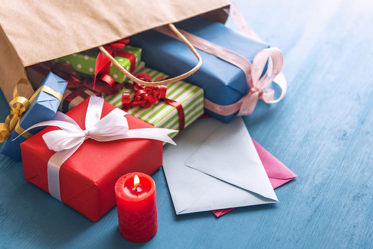 Gift bag overturned on the table - Shopping bag full of colorful presents, paper wrapped and tied with ribbon and bows, overturned on a blue wooden table, over closed envelopes, near a red candle. New Year Valentine's Day  Wooden Table Blue Background Box - Container Candlelight Celebration Christmas Christmas Present Close-up Expenses Gift Gifting Greeting Card  High Angle View Holiday Shopping Indoors  Multi Colored Ribbon - Sewing Item Table Tied Bow Wrapped Wrapping Paper