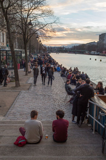 People sitting at riverbank against sky during sunset