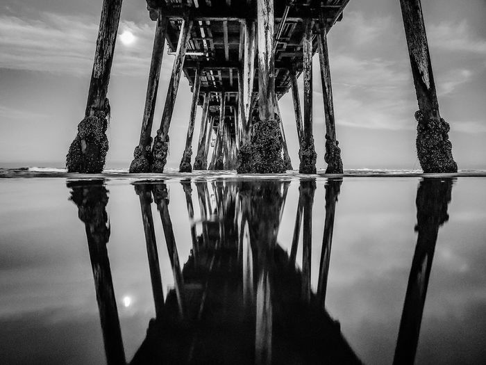 Reflection of pier on sea against sky