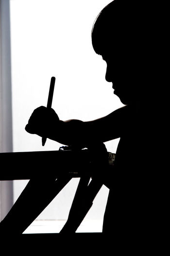 6 year old boy drawing at table. Boy And Girl Creativity Day Drawing Human Hand Indoors  One Person Silhouette Vertical