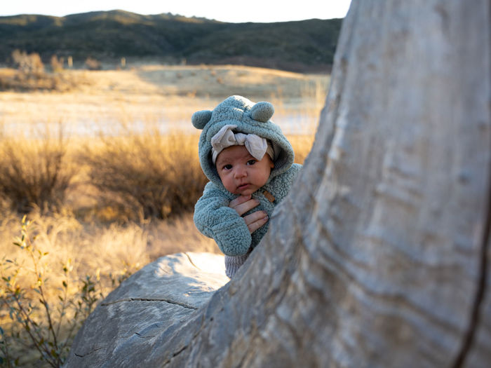 Portrait of cute baby girl behind tree trunk
