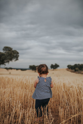 Rear view of baby girl standing on land against sky