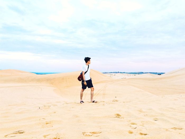 Full length of man walking on desert against sky