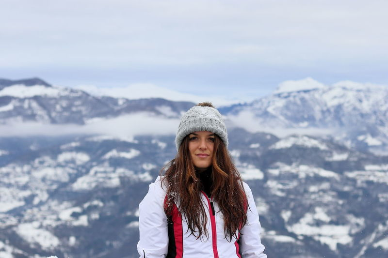 Portrait of smiling woman standing on snowcapped mountain