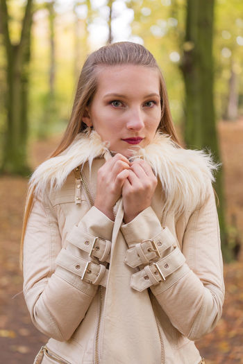 Portrait of young beautiful woman wearing jacket against autumn trees
