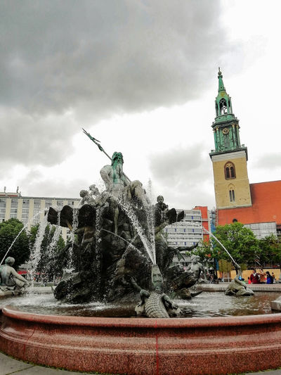 Fountain in front of building against sky
