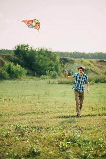 Full length of man flying kite on grassy field against sky