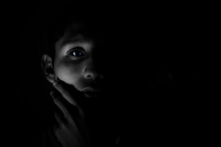 Close-up portrait of teenage girl in darkroom