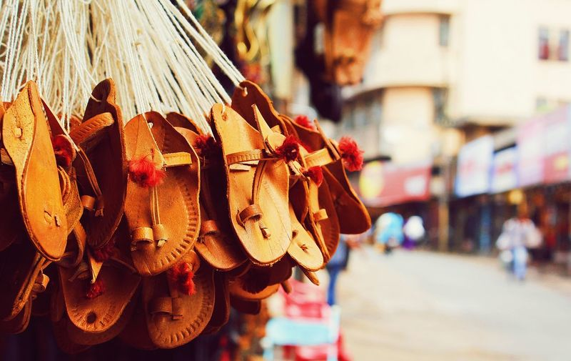 Close-up of flip-fop hanging in market for sale