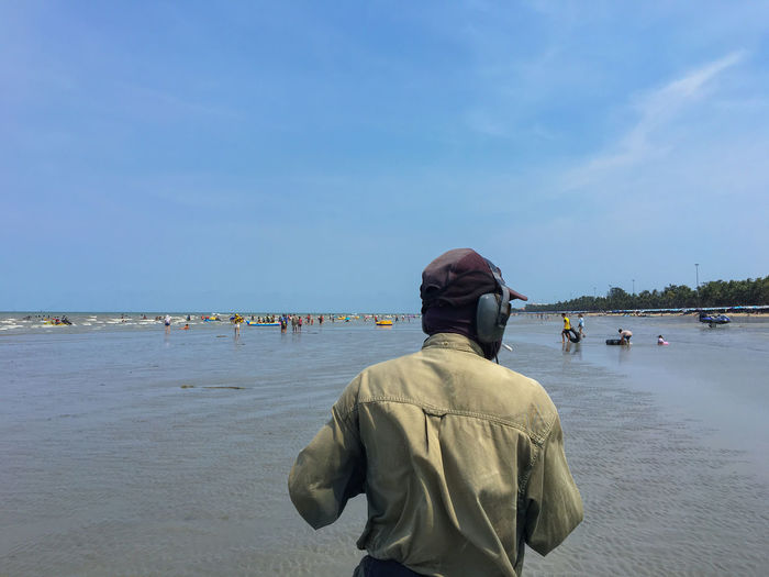 Rear view of guard standing at beach against sky