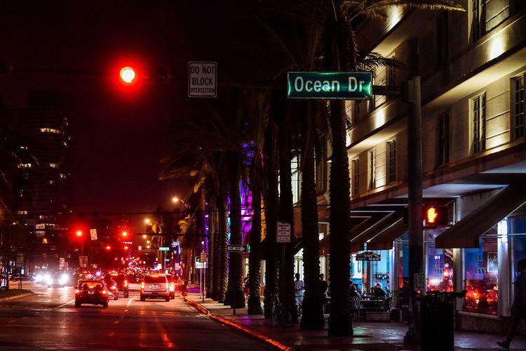 Illuminated road amidst city at night