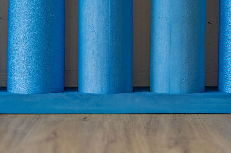 Blue pilates roll with white brick wall. for balance- and stabilisation exercises. close up.