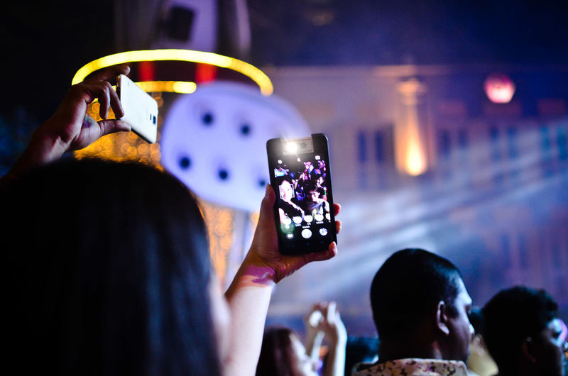 Rear view of young man photographing through smart phone at night