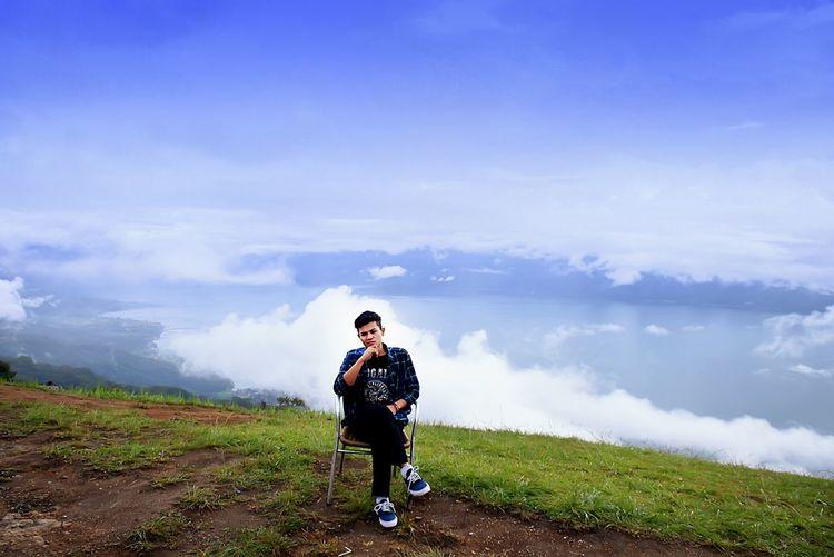 Full Length Of Man On Chair On Hill Against Sky