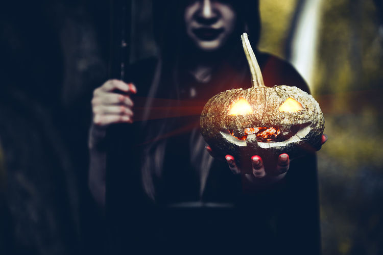 Midsection of woman in witch costume holding illuminated jack o lantern