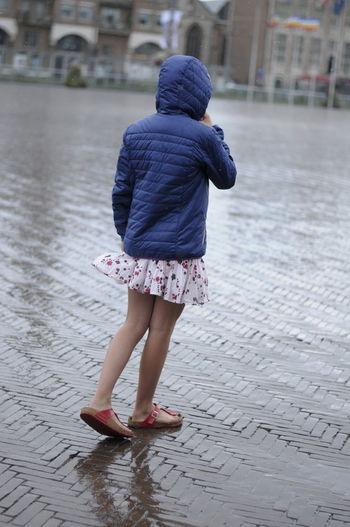 Rear view of girl wearing raincoat walking on wet road