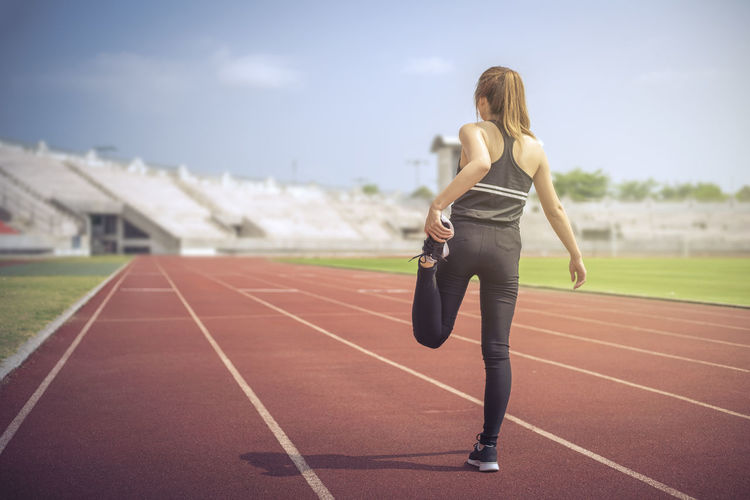 Rear view of woman on running track against sky