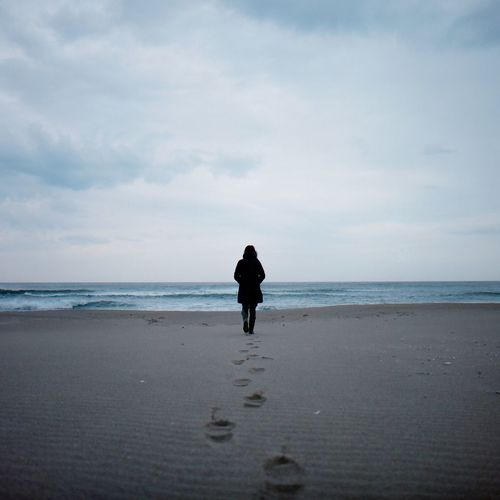 Rear view of a woman walking on beach