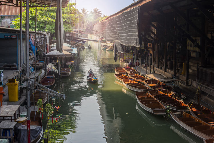 Boats moored in canal amidst buildings
