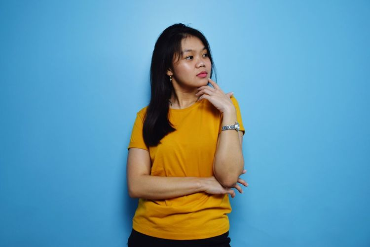 Young woman looking away while standing against blue background