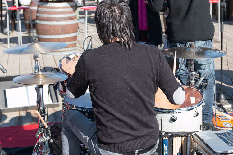 Drum Drummer Music Adult Bicycle Business Casual Clothing City Concert Day Focus On Foreground Hairstyle Incidental People Men Mode Of Transportation Musical Instrument Occupation One Person Real People Rear View Small Business Standing Three Quarter Length Transportation