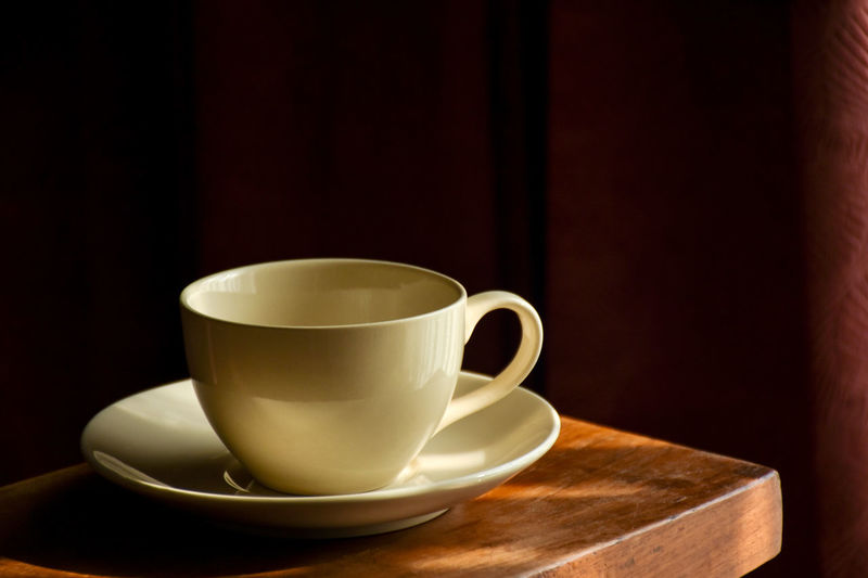 Empty coffee cup with saucer prepared for coffee time, dark corner background. Afternoon Coffee Break Beverage Coffee Time Espresso Porcelain  Pouring Sunlight Close-up Coffee - Drink Coffee Break Coffee Cup Corner Drink Empty Cup Fill Food And Drink Freshness Indoor Low Key Lighting Refreshment Saucer Table Wood - Material