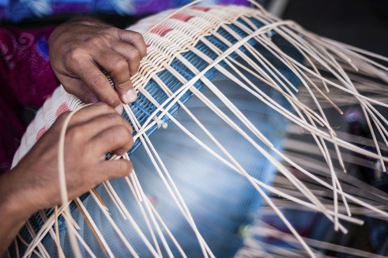 Cropped image of person weaving wicker basket