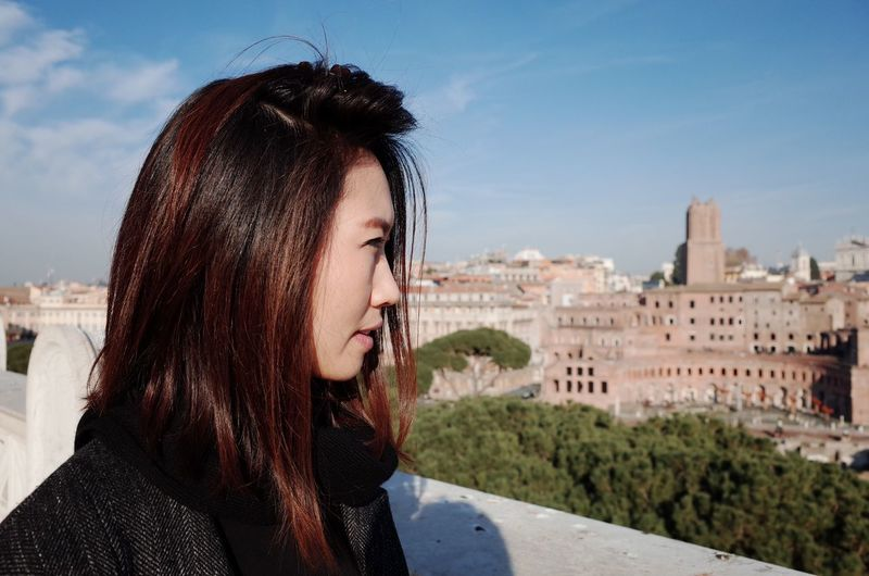 Close-up portrait of woman with cityscape against sky