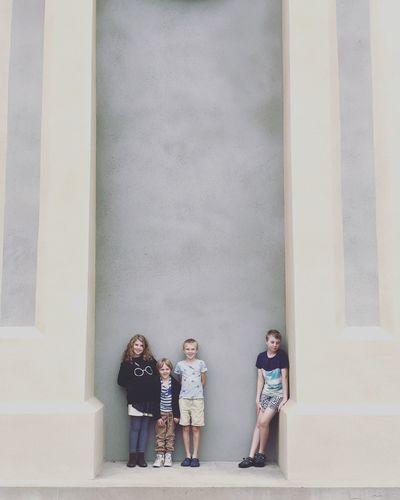 Children standing against wall
