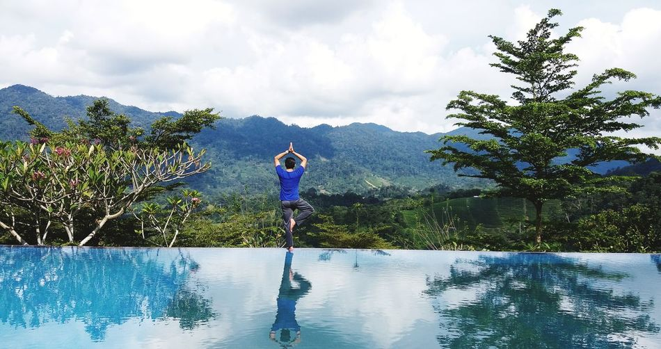 Rear View Of Man Doing Yoga By Swimming Pool Against Sky