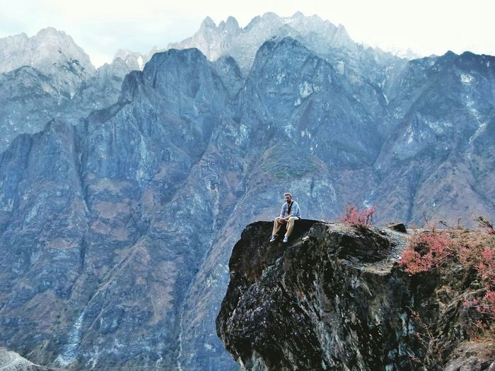 Low angle view of man sitting on cliff against mountains at tiger leaping gorge