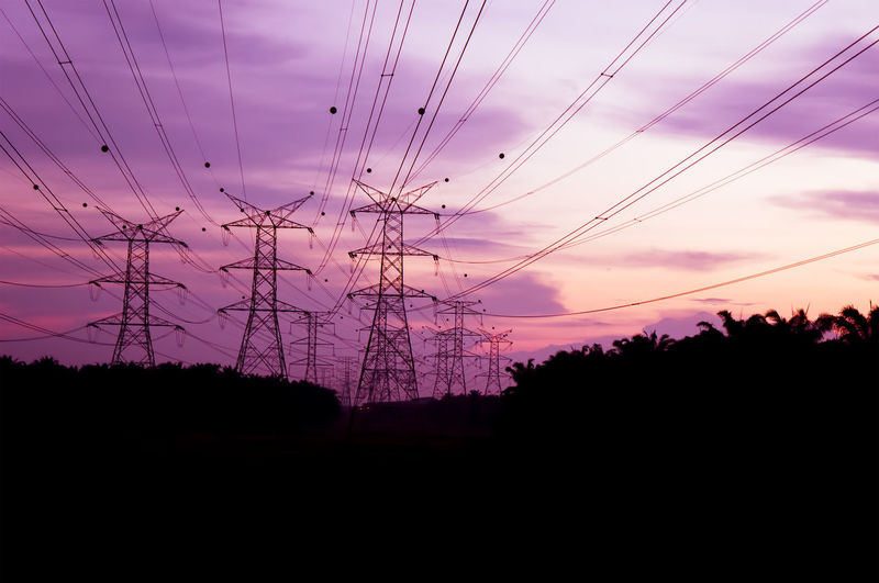 Silhouette of a electricity pylons at sunset Power Plant Transmission Watt Beauty In Nature Cable Connection Electric Grid Electricity  Electricity Pylon Engineering Environment Fuel And Power Generation Landscape Nature Outdoors Power Line  Power Supply Silhouette Sky Sunset Technology Tranquility Tree Volt Voltage