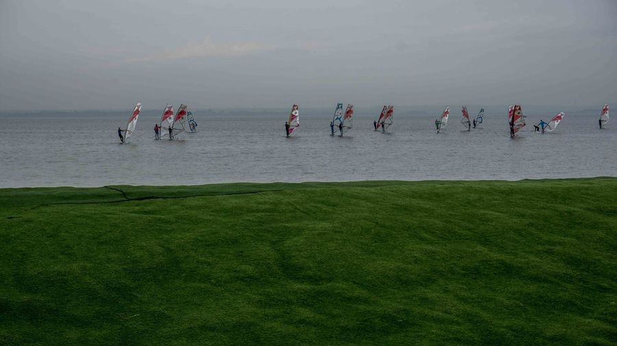 People Windsurfing On Sea Against Cloudy Sky