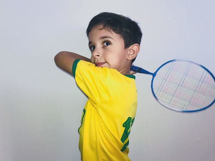 Boy standing against yellow background