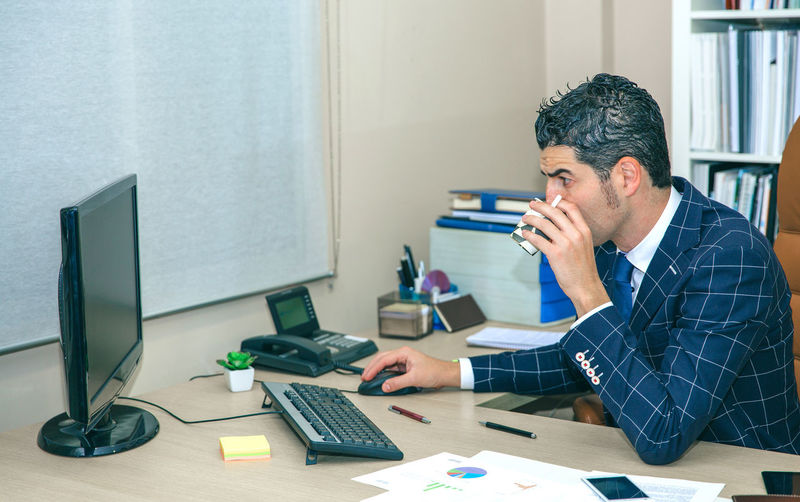 Businessman drinking cup of coffee while working with computer in the office Business Busy Company Horizontal Man Suit Working Business Finance And Industry Businessman Caucasian Chairman Chief Concentration Device Executive  Headquarters Jacket Job Male One Person Portrait Serious Smart Phone Sucess Technology