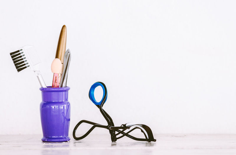 Close-up of make-up tools on table against white background