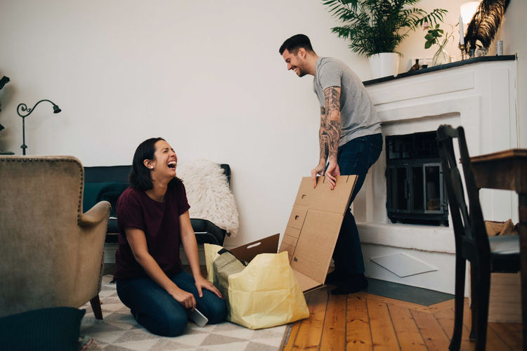 Cheerful couple unpacking boxes in living room at new home