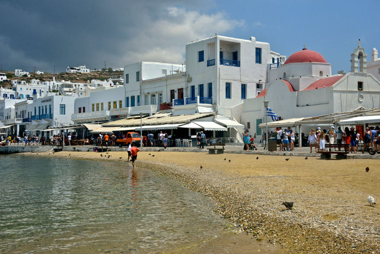 cityscape near the beach and tourists relaxing and refreshing in the sea of Chora Building Exterior Architecture Built Structure Sky Group Of People Crowd Water Large Group Of People Real People Building City Nature Beach Lifestyles Men Cloud - Sky Waterfront Day Outdoors Mykonos,Greece Chora Greek Islands Greek Architecture Sea Seafront Travel Destinations Colored Roof Summertime Seaview Urban Village Street Photography