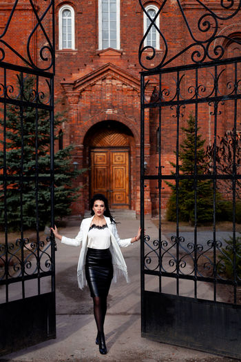 Full length of beautiful woman standing at gate entrance against historic building
