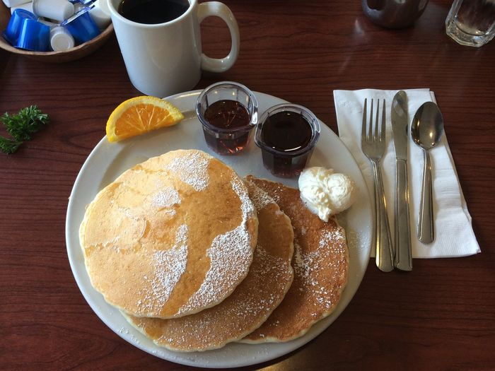 High angle view of pancakes by syrup in plate on table