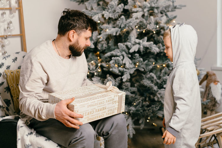 Young man sitting on christmas tree