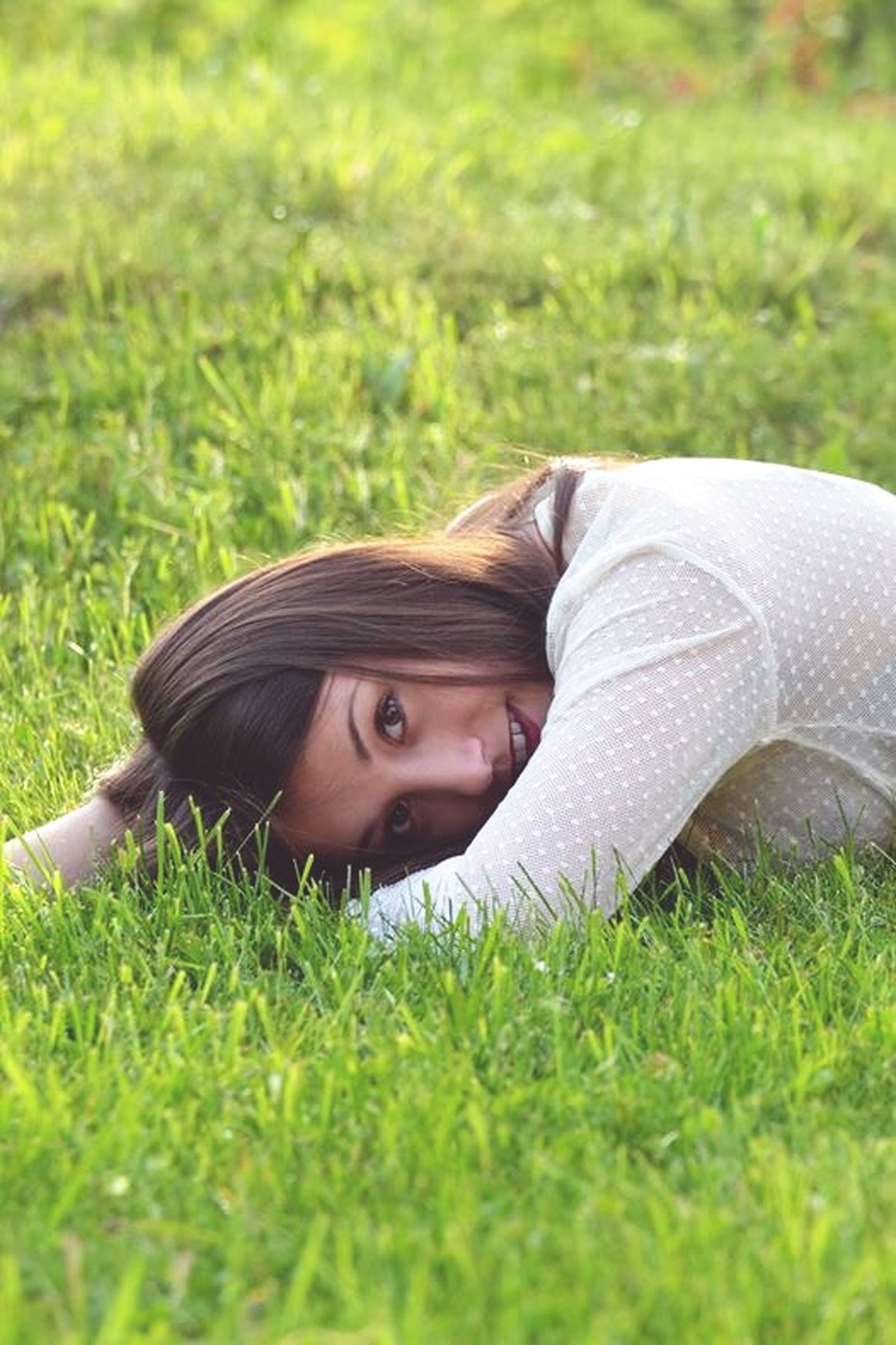 grass, person, lifestyles, leisure activity, relaxation, young adult, field, grassy, casual clothing, young women, portrait, lying down, looking at camera, headshot, smiling, childhood, green color, innocence