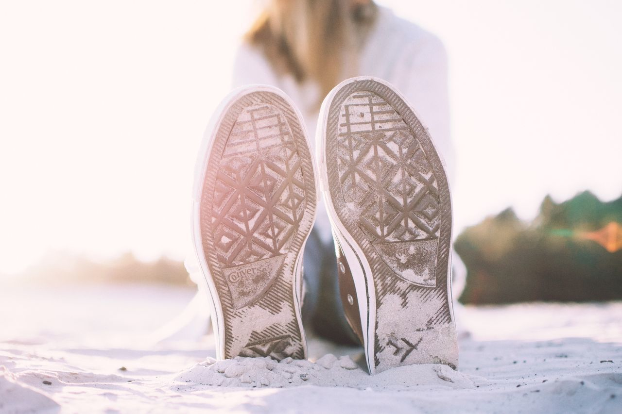 Low Section Of Woman Wearing Shoes And Sitting On Beach