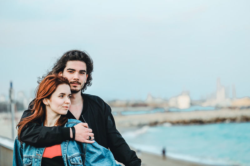 Happy young couple enjoying sea view on a warm spring day. Handsome man gently hugs his beautiful redhead sweetheart. Two People Young Adult Lifestyles Portrait Real People Young Women Togetherness Couple - Relationship Positive Emotion Love Couple Young Couple In Love Together Springtime Sea Beach Water Standing Focus On Foreground People Looking At Camera Young Men Casual Clothing Adult Nature Outdoors My Best Photo